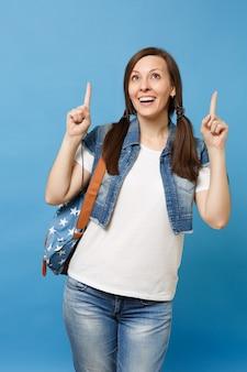 Portret van jonge vrolijke aantrekkelijke vrouw student in denim kleding met rugzak op zoek wijzende wijsvingers omhoog geïsoleerd op blauwe achtergrond. onderwijs op de middelbare school. kopieer ruimte voor advertentie.