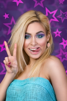 Portret van jonge vrolijke blonde vrouw die haar tong en overwinningsteken toont