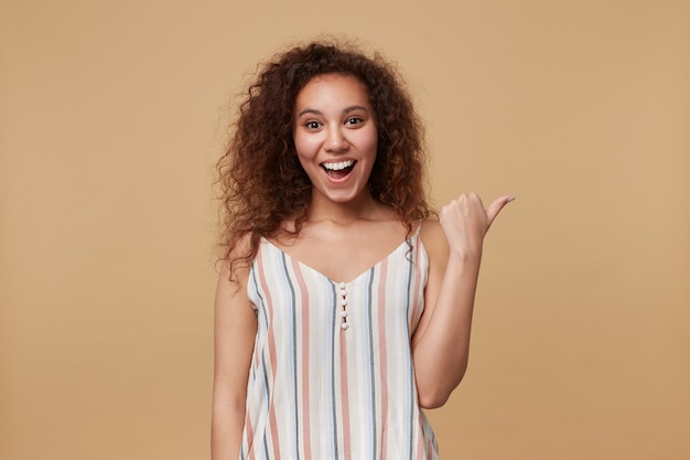 Portret van jonge vrolijke bruinharige krullende vrouw die vrolijk lacht terwijl ze met de duim opzij wijst, geïsoleerd op beige in zomer gestreepte top