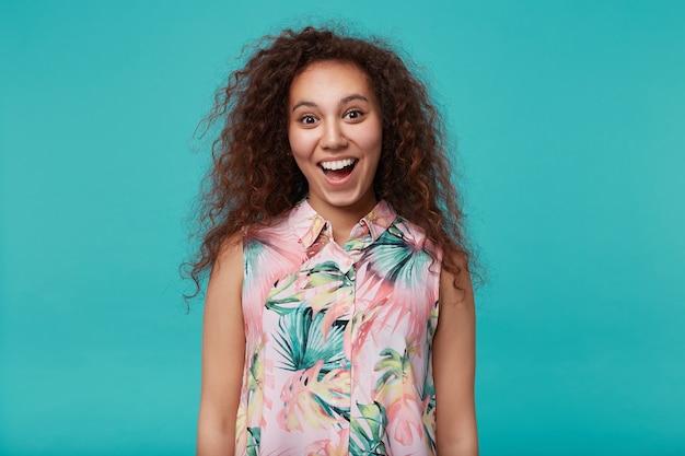 Portret van jonge vrolijke bruinogige langharige krullende brunette vrouw die gelukkig kijkt met brede mond geopend terwijl poseren blauw met handen naar beneden