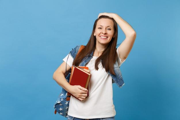Portret van jonge vrolijke lachende studente met rugzak die haar kapsel aanraakt en schoolboeken vasthoudt die op blauwe achtergrond worden geïsoleerd. onderwijs in het concept van de middelbare schooluniversiteit.