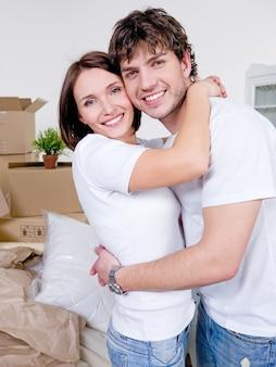 Portret van jonge vrolijke liefdevolle paar met een gelukkige glimlach in nieuw huis