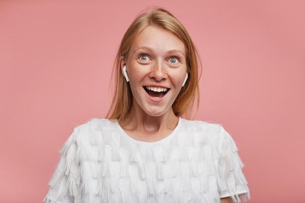 Portret van jonge vrolijke mooie roodharige vrouw met casual kapsel die oortelefoons draagt terwijl ze over roze achtergrond staat, haar groen-grijze ogen rondt terwijl ze gelukkig naar boven kijkt