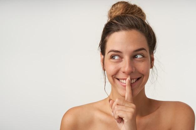 Portret van jonge vrolijke vrouw die opzij kijkt met een brede glimlach, beweert geheim te houden, wijsvinger dichtbij lippen houdt, geïsoleerd op wit
