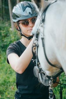 Portret van jonge vrolijke vrouw met paard bij de zomer