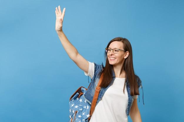 Portret van jonge vrolijke vrouw student in glazen met rugzak opzij kijken zwaaiende hand voor begroeting, vriend ontmoeten geïsoleerd op blauwe achtergrond. onderwijs in het concept van de middelbare schooluniversiteit.