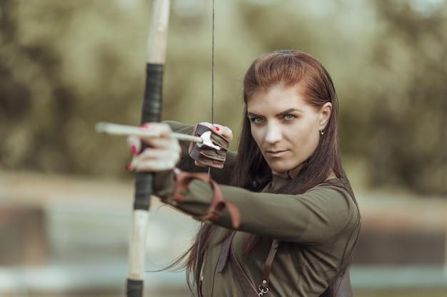 Portret van jonge vrouw boogschieten op bos achtergrond