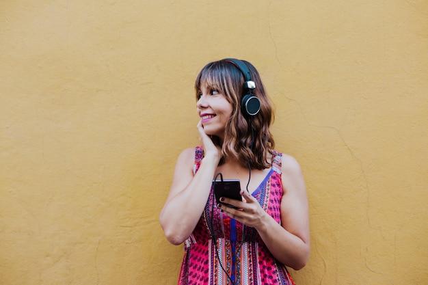 Portret van jonge vrouw die aan muziek op hoofdtelefoon en mobiele telefoon luistert