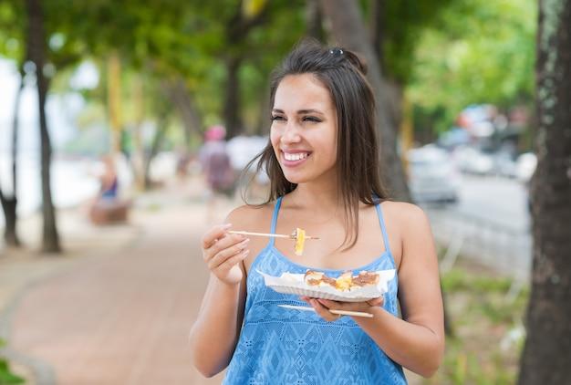 Portret van jonge vrouw die aziatisch straatvoedsel eten terwijl het lopen