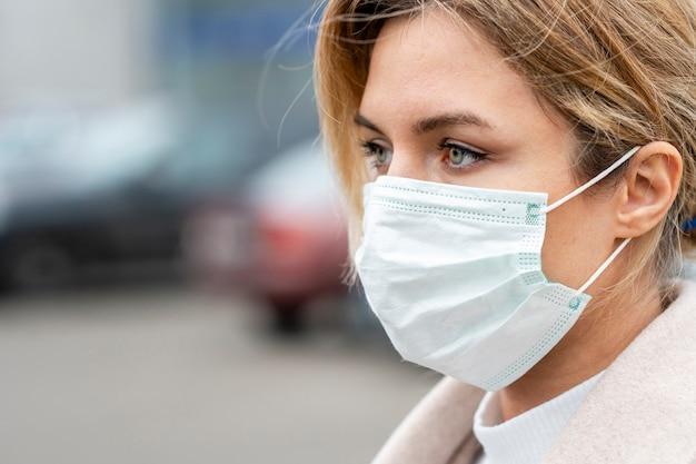 Portret van jonge vrouw die chirurgisch masker draagt