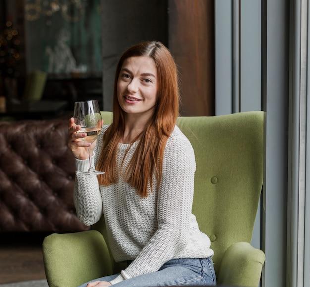 Portret van jonge vrouw die een glas wijn heeft