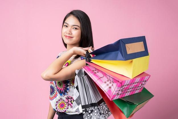 Portret van jonge vrouw die kleurrijke het winkelen zakken met glimlach draagt