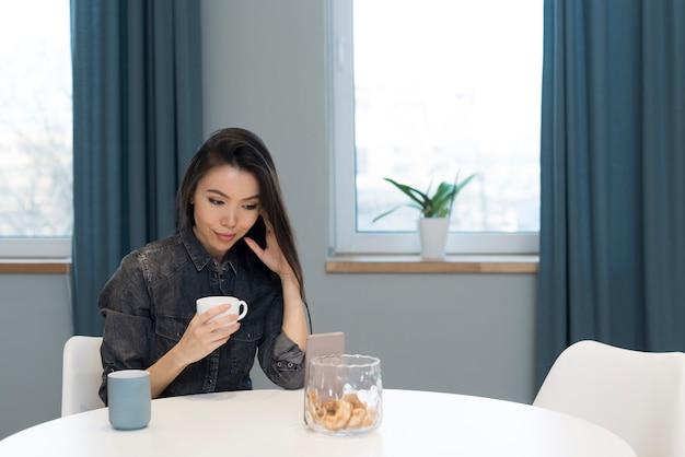 Portret van jonge vrouw die koffie heeft thuis
