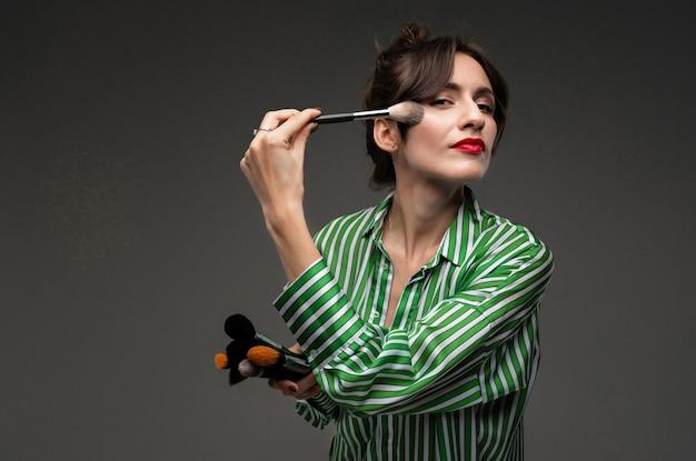 Portret van jonge vrouw die op make-up op jukbeenderen in gestreepte lated blouse zetten