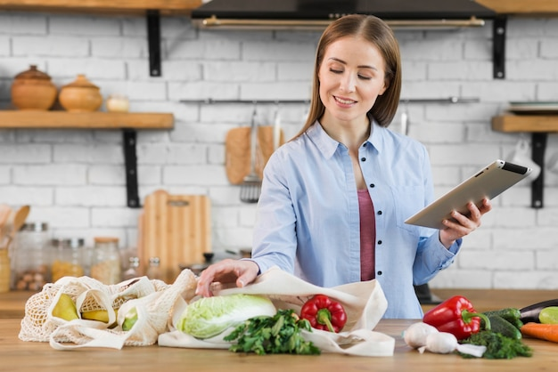 Portret van jonge vrouw die organische kruidenierswinkels controleert