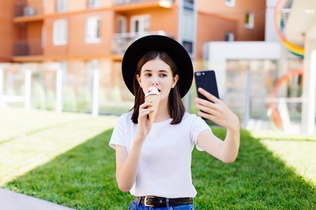 Portret van jonge vrouw die roomijs eten en selfie foto op camera in de zomerstraat nemen.