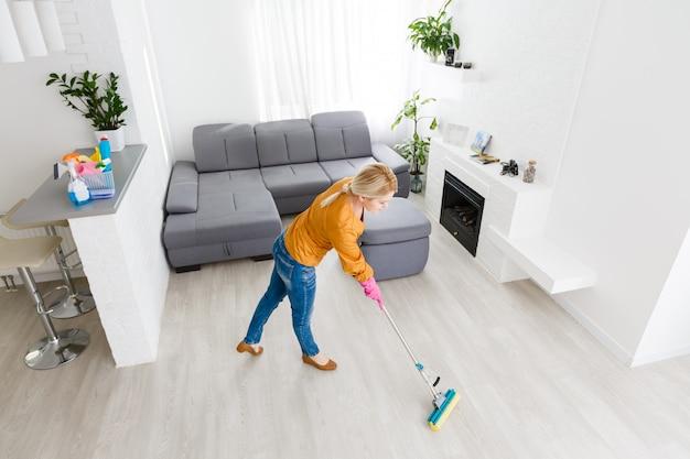 Portret van jonge vrouw die vloer thuis dweilen