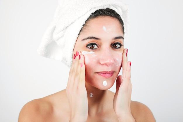 Portret van jonge vrouw die vochtinbrengende crème op haar gezicht toepast dat op witte achtergrond wordt geïsoleerd