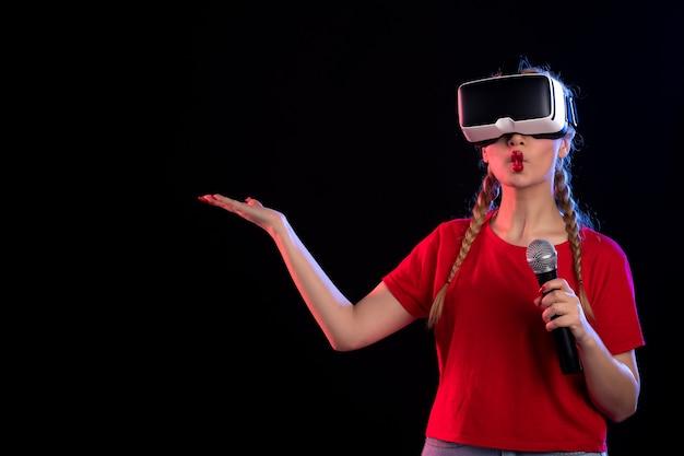 Portret van jonge vrouw die vr speelt en zingt met mic donkere visuele muziekgames