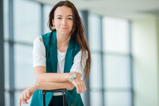 Portret van jonge vrouw een luchthavenzitkamer die op het inschepen wachten