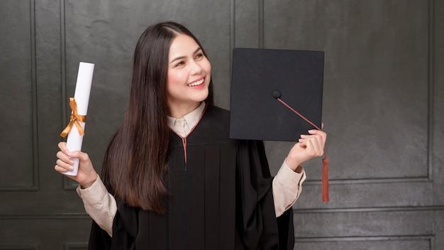 Portret van jonge vrouw in graduatietoga die en op zwarte achtergrond glimlachen toejuichen