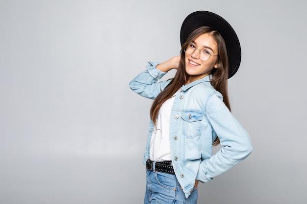 Portret van jonge vrouw in zwarte slappe hoed dat op witte muur wordt geïsoleerd