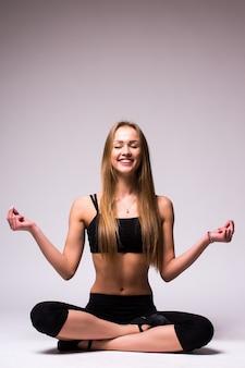 Portret van jonge vrouw mediteren in pose van lotus geïsoleerd