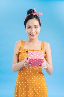 Portret van jonge vrouw met geschenkdoos op blauw on