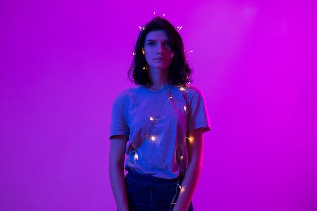 Portret van jonge vrouw met hangende kerstmislichten op haar lichaam