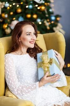 Portret van jonge vrouw met kerstmis huidige dozen voor kerstmisboom