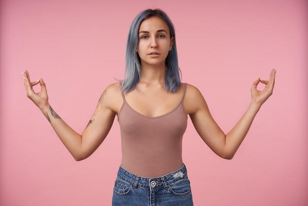 Portret van jonge vrouw met kort blauw haar vouwen met opgeheven vingers namaste teken terwijl staande op roze in beige overhemd