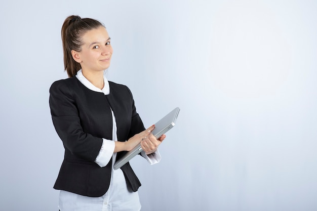 Portret van jonge vrouw met laptop over witte muur.