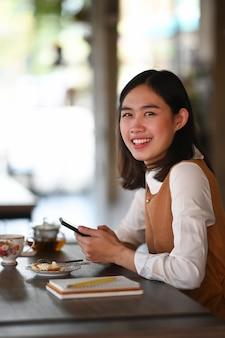 Portret van jonge vrouw met mobiele telefoon en glimlachen