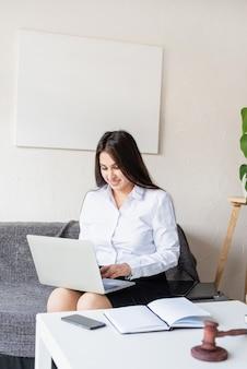 Portret van jonge vrouwelijke advocaat die bij laptop zittend op de bank werkt