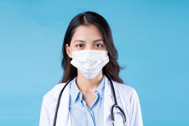 Portret van jonge vrouwelijke arts, geïsoleerd op blauwe achtergrond blue