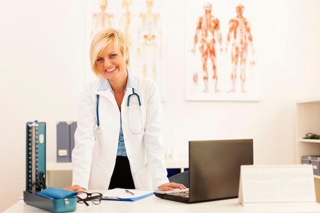 Portret van jonge vrouwelijke arts in haar kantoor