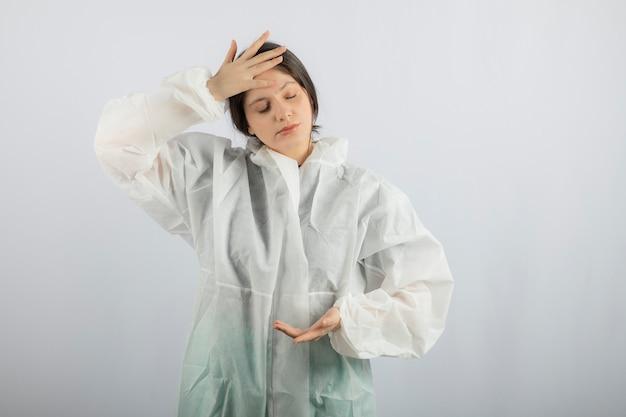 Portret van jonge vrouwelijke arts-wetenschapper in defensieve laboratoriumjas die temperatuur controleert.