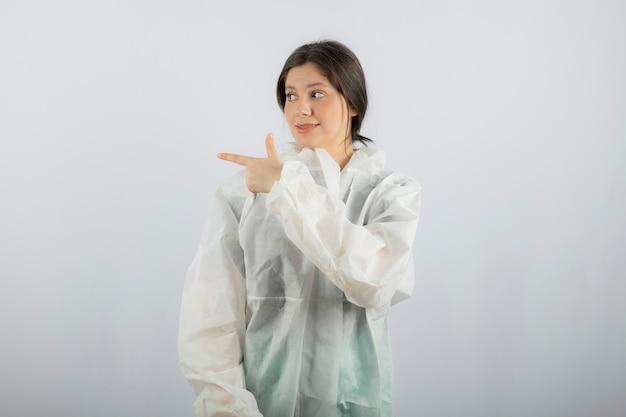 Portret van jonge vrouwelijke arts-wetenschapper in defensieve laboratoriumjas die weg wijst.