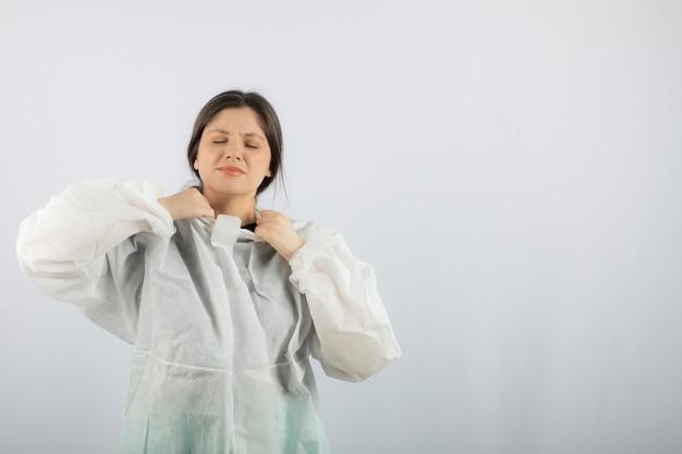 Portret van jonge vrouwelijke arts wetenschapper in defensieve laboratoriumjas poseren.