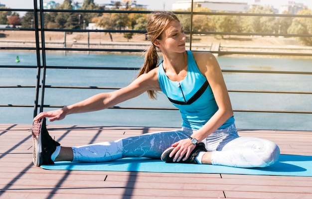 Portret van jonge vrouwelijke atleet die haar beenzitting uitrekt bij openlucht