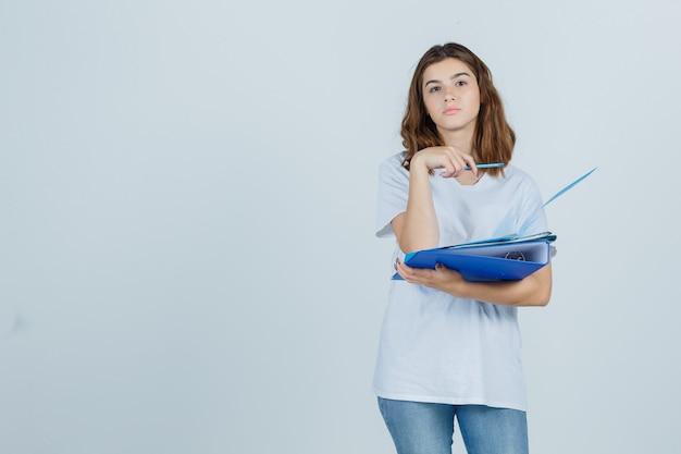 Portret van jonge vrouwelijke bedrijfsmappen en pen in wit t-shirt, spijkerbroek en op zoek peinzend vooraanzicht