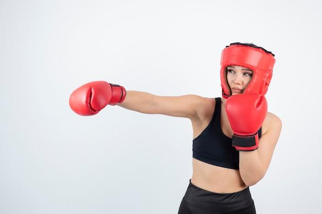 Portret van jonge vrouwelijke bokser in rode handschoenen en helmgevechten.