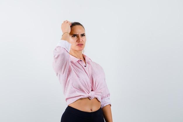 Portret van jonge vrouwelijke hoofd krabben in casual shirt, broek en op zoek doordachte vooraanzicht