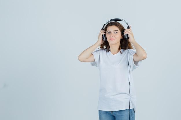 Portret van jonge vrouwelijke koptelefoon in wit t-shirt, spijkerbroek opstijgen en op zoek dromerig vooraanzicht