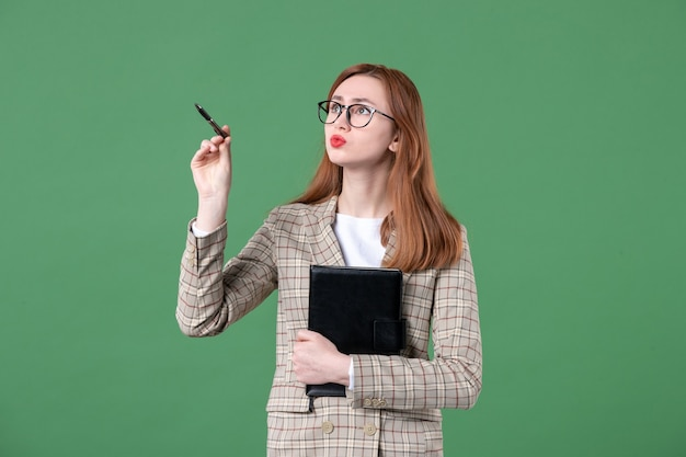 Portret van jonge vrouwelijke leraar in pak met notitieblok op groen