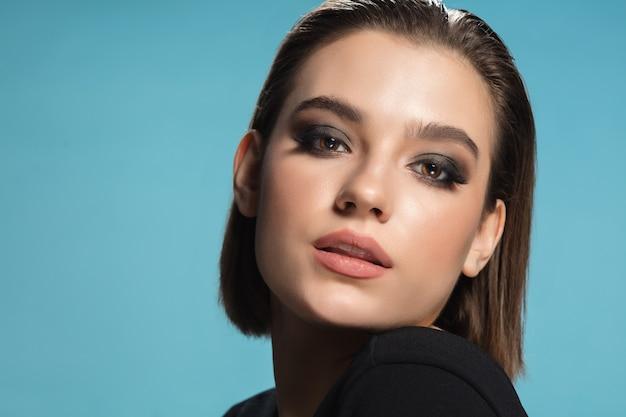 Portret van jonge vrouwelijke mannequin geïsoleerd op blauwe achtergrond.