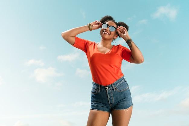 Portret van jonge vrouwelijke mannequin op blauwe hemelachtergrond.