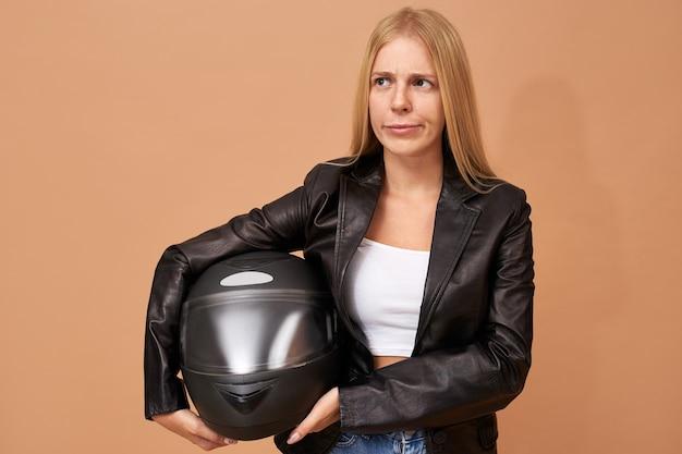 Portret van jonge vrouwelijke ruiter met beugels tanden en lang steil haar poseren geïsoleerd in zwart lederen jas
