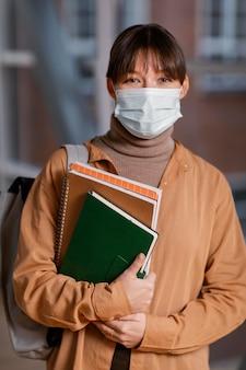 Portret van jonge vrouwelijke student die een medisch masker draagt