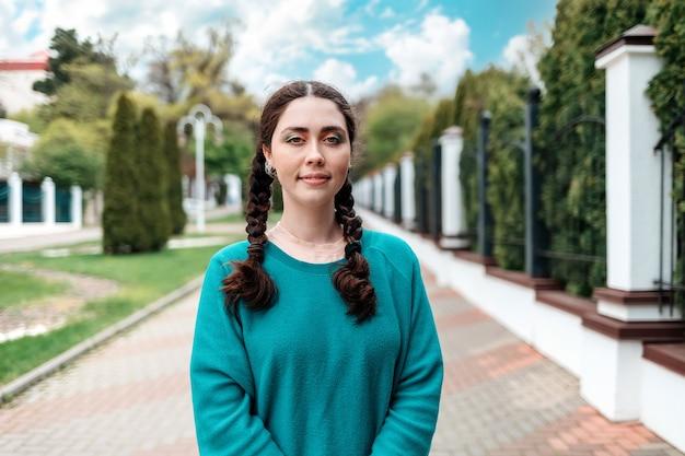 Portret van jonge vrouwelijke student met staartjes staat op straat, bij de ingang van de universiteit. openlucht, omheining. het concept van toelating van studenten tot de universiteit.
